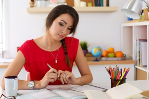 47986718 - female student at workplace portrait holding pen and looking in textbooks studying. woman writing letter, list, plan, making notes, doing homework. education, self development and perfection concept