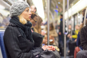 41697826 - beautiful blonde caucasian lady, wearing winter coat, traveling by metro in rush hour. public transport.
